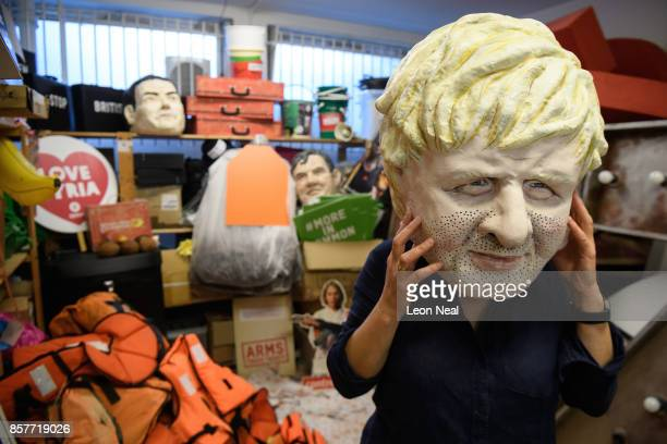 Lisa Rutherford of Oxfam poses with a mask of Foreign Secretary Boris Johnson while surrounded by assorted props used in political campaigns in the...