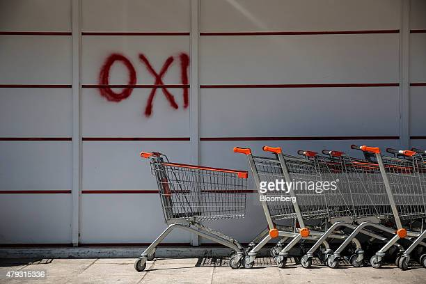 An 'OXI' or 'No' campaign graffiti sign against bailout proposals sits on the wall of a local supermarket above shopping carts in Athens Greece on...