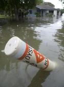 An oyster reef marker floats in the back yard of a flooded home ahead of Hurricane Ike's arrival September 12 2008 in Seabrook Texas An advisory for...