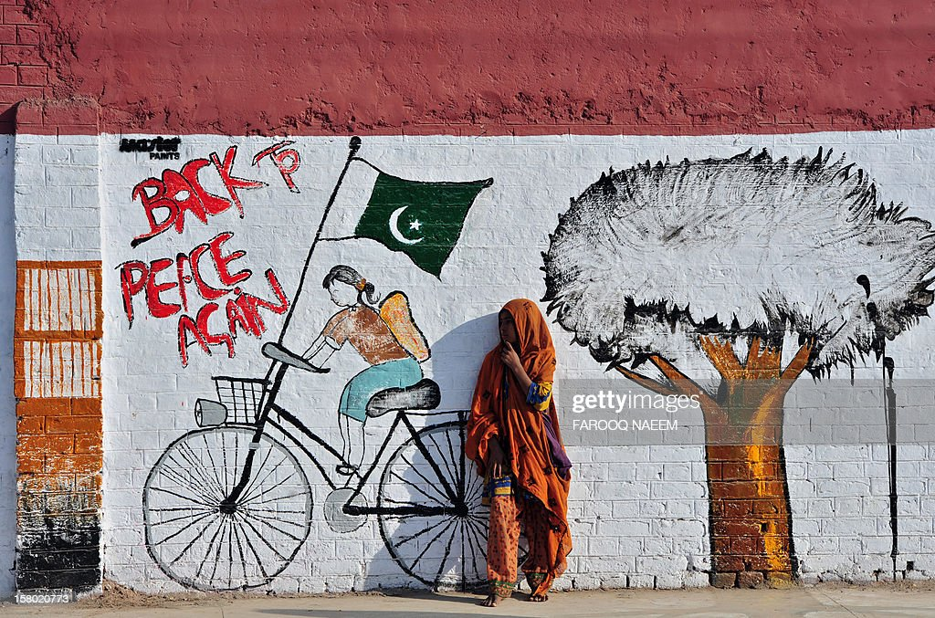 An Pakistan beggar stands in front of a mural on the streets of Rawalpindi on December 9, 2012. Pakistan's growth remains too weak, underlying inflation is high and the trade balance is heading in the wrong direction, the IMF said in a statement. AFP PHOTO/Farooq NAEEM
