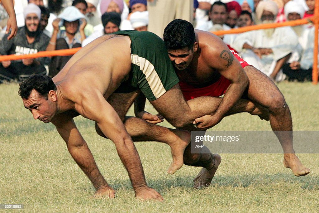 An Pakistani Punjab kabbadi player (L) is tackled by his Indian opponent during the 2008 Sri Guru Gobind Singh Kabaddi Series in Gopalpur Majwind village, some 25 kms from Amritsar on November 9, 2008. India won the match against Pakistan in the sporting event dedicated to the tri-centenary of the Sri Guru Granth Sahib?s coronation. Kabbadi, a team sport which originated in the Indian sub-continent, involves team members making 'raids' into the opposing team's territory on a playing field in an attempt to 'tag' opponents while holding one's breath.