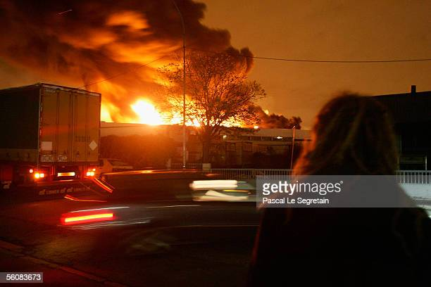 An passer by looks on at a warehouse set ablaze in the early hours on November 4 2005 in AulnaysousBois Paris France Riots continue on the eighth...