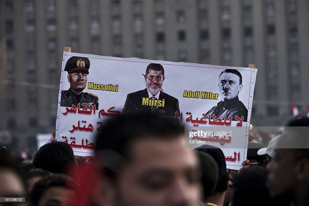 An poster likening Egyptian President Mohammed Morsi to Benito Mussolini and Adolf Hitler is held above the heads of demonstrators in Tahrir Square on Friday, November 30, 2012, in Cairo, Egypt. Demonstrations continue in Cairo today after Egypt's Constituent Assembly finalised a draft of the country's new constitution in an overnight voting session late on Thursday. Violent protests have continued for over ten days across the country in response to Egyptian president Mohammed Morsi having awarded himself new constitutional powers, which many believe have been pushed through by the Muslim Brotherhood without inclusive consultation with other members of Egypt's cabinet and political leadership. (Photo by Ed Giles/Getty Images).