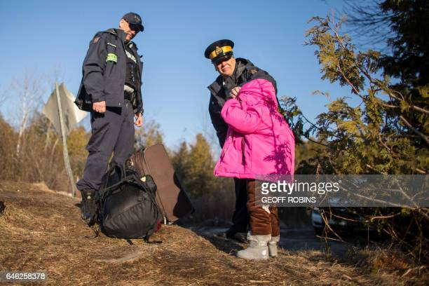 An RCMP officer adjusts the hood of a little girl part of family of four from Pakistan after they illegally crossed the USCanada border near...