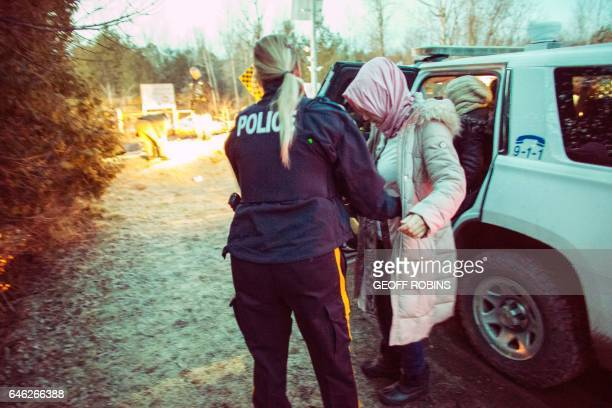An RCMP officer pats down a woman from an extended family of seven people from Turkey into custody after they illegally crossed the USCanada border...