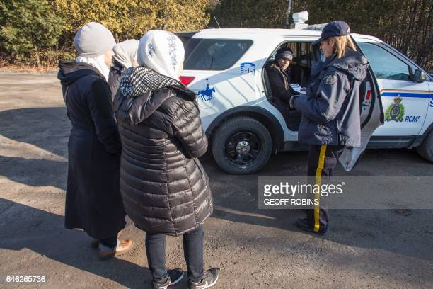 An RCMP officer reads a family of five from Syria their rights after they were arrested for illegally crossing the USCanada border near Hemmingford...