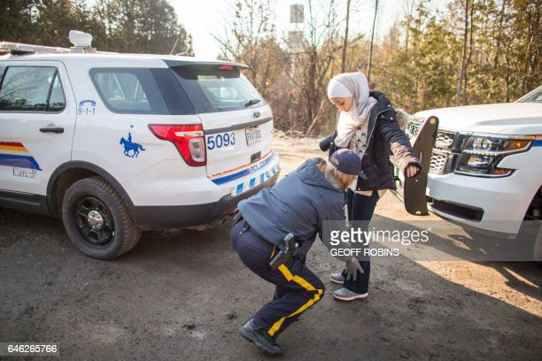 An RCMP officer searches a Syrian girl after she and her family illegally crossed the USCanada border near Hemmingford Quebec February 28 2017 / AFP...