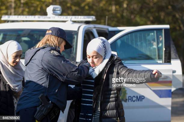An RCMP officer searches an 18 yearold Syrian woman after she and her family illegally crossed the USCanada border near Hemmingford Quebec February...