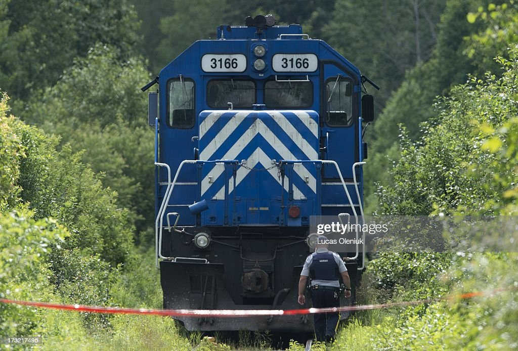 An RCMP officer secures a grouping of locomotives that were involved in the Lac-MÈgantic derailment on the tracks leading to the crash sight. The area is being considered a crime scene.