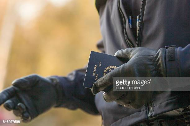 An RCMP officers holds the passport of a woman from Eritrea after she illegally crossed the USCanada border near Hemmingford Quebec February 28 2017...