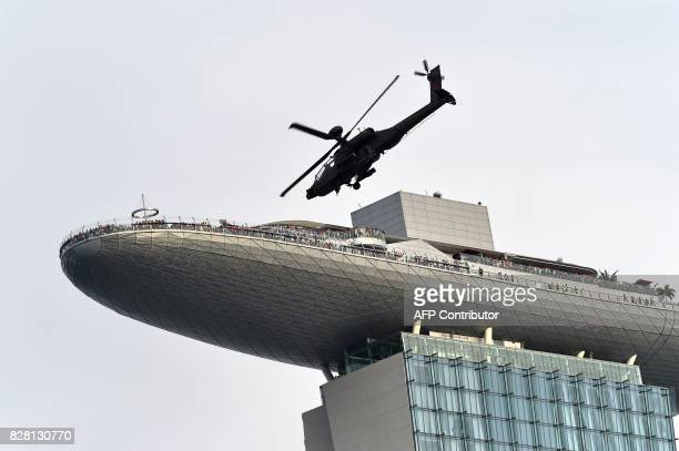 An Republic of Singapore Air Force Apache helicopter flies past the Marina Bay Sands during the 52nd National Day parade and celebration in Singapore...