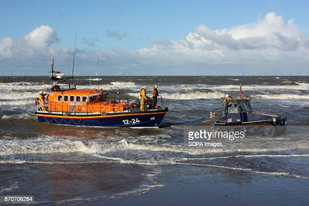 An RNLI crewmember secures a static guidline to the wheeled cradle that moments before hoisted the Mersey Class 550hp Rhyl Lifeboat up ithe Lifeboat...