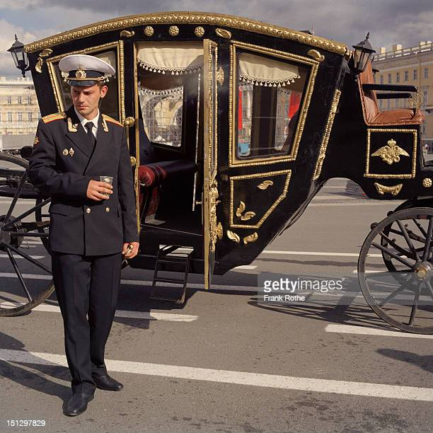 an Russian officer stands beside an old chaise