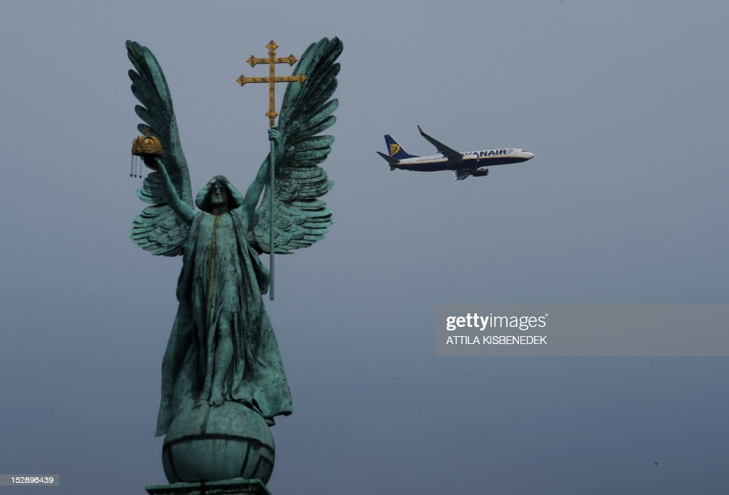 An Ryanair airplane flies behind a statue of the Archangel Gabriel standing on a 36 metre high Corithian Column in Budapest's Heroes' square on September 27, 2012.