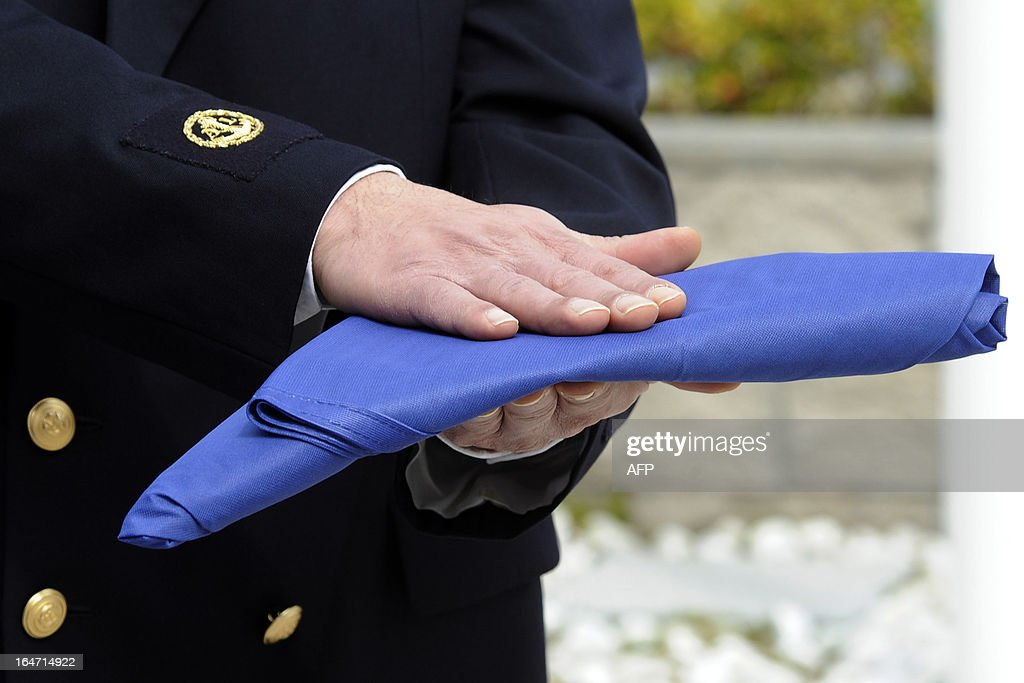 An sailorman officer folds a flag during the deactivation ceremony of Navsouth Base Headquarter in Nisida Island near Naples on March 27, 2013. The new NAVSOUTH headquarter will be based at Northwood in United Kingdom.