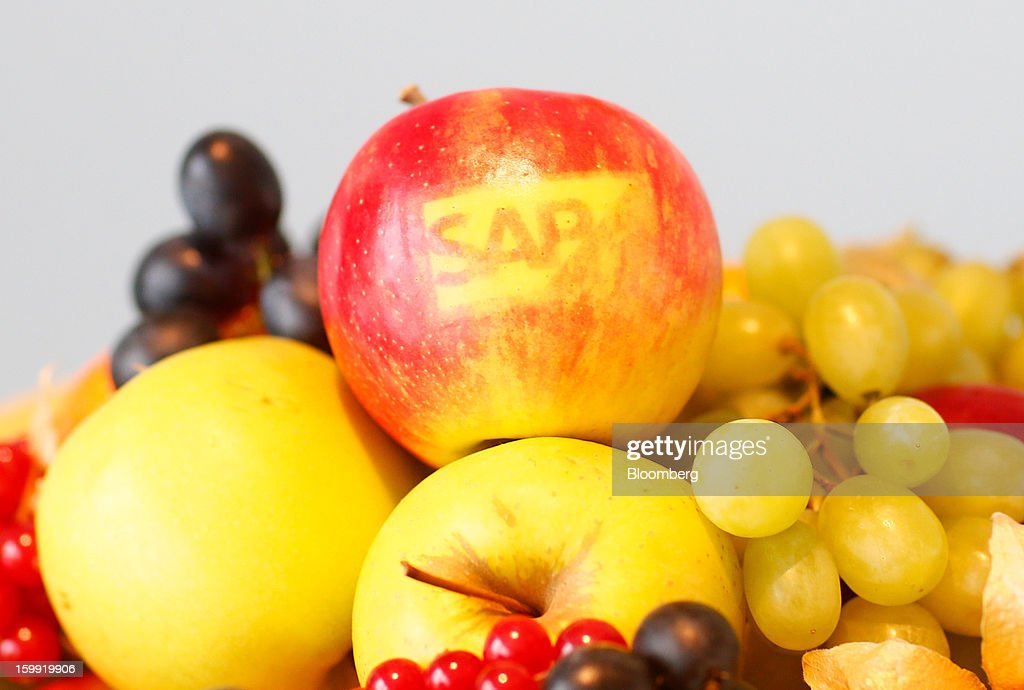An SAP AG company logo sits on an apple displayed at a buffet during a news conference in Walldorf, Germany, on Wednesday, Jan. 23, 2013. SAP AG, the biggest maker of business-management software, forecast at least a 12 percent gain in full-year earnings as it adds Internet-based programs to attract users and fend off competition from Oracle Corp. Photographer: Ralph Orlowski/Bloomberg via Getty Images