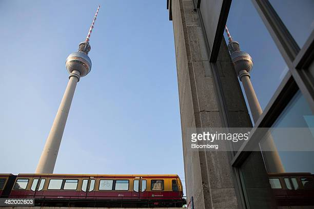 An SBahn passenger train passes beneath the Fernsehturm television tower the city's tallest structure off Alexanderplatz square in Berlin Germany on...