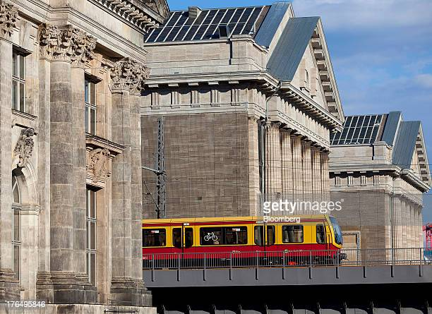 An SBahn train operated by Deutsche Bahn AG passes over a bridge spanning the River Spree between the Pergamon Museum right and Bode Museum left in...