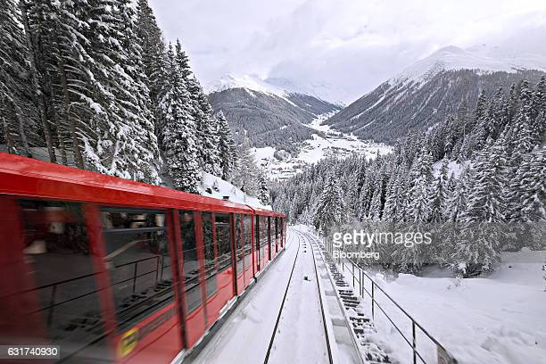 An SBB AG train makes its way between snow covered trees towards the town of Davos the venue for the World Economic Forum in Davos Switzerland on...
