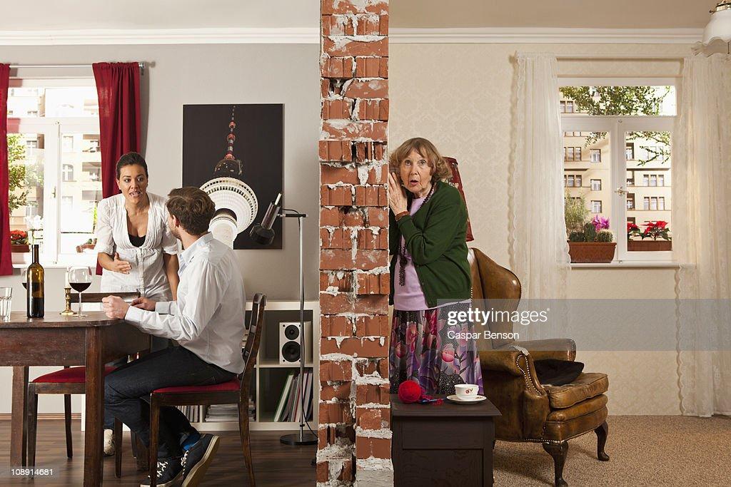 An senior woman listening to her neighbors arguing
