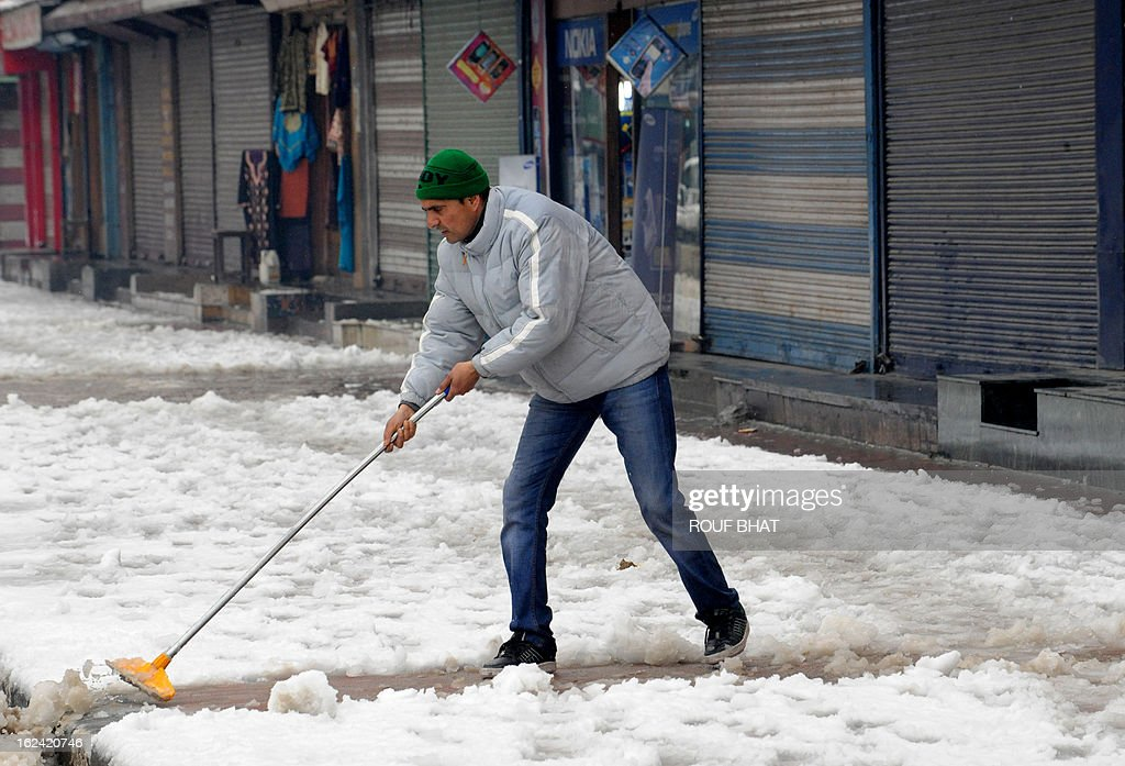 An shopkeeper clears the road after a snowfall in Srinagar on February 23, 2013. The Jammu-Srinagar National Highway remained closed for the second day as fresh snowfall across Kashmir prompted authorities to issue an avalanche warning in higher reaches of the Valley. AFP PHOTO/ Rouf BHAT