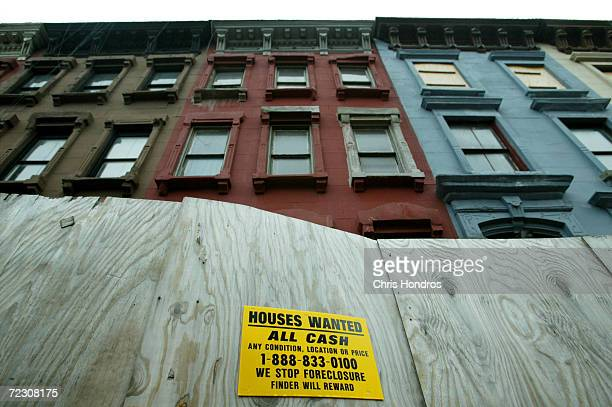 An sign advertising for 'Houses Wanted' stands on a temporary wall in front of row houses November 6 2003 in the Harlem neighborhood of New York City...