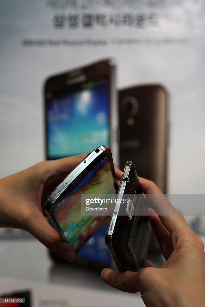 An SK Telecom Co. employee holds a Samsung Electronics Co. Galaxy Round smartphone, left, and a Samsung Galaxy Note 3 smartphone, right, for a photograph at an SK Telecom boutique in the Jongro-gu area of Seoul, South Korea, on Friday, Oct. 11, 2013. Samsung will sell what it called the worlds first smartphone with a curved display as the largest handset maker moves toward devices with bendable screens in its competition with Apple Inc. Photographer: Woohae Cho/Bloomberg via Getty Images