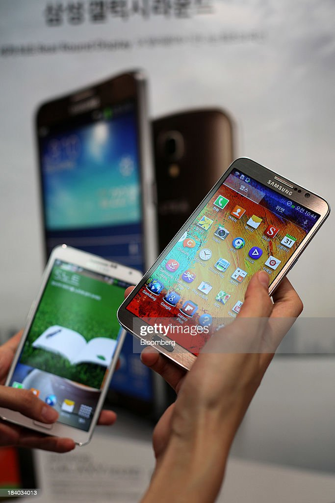An SK Telecom Co. employee holds a Samsung Electronics Co. Galaxy Round smartphone, right, and a Samsung Galaxy Note 3 smartphone, left, for a photograph at an SK Telecom boutique in the Jongro-gu area of Seoul, South Korea, on Friday, Oct. 11, 2013. Samsung will sell what it called the worlds first smartphone with a curved display as the largest handset maker moves toward devices with bendable screens in its competition with Apple Inc. Photographer: Woohae Cho/Bloomberg via Getty Images