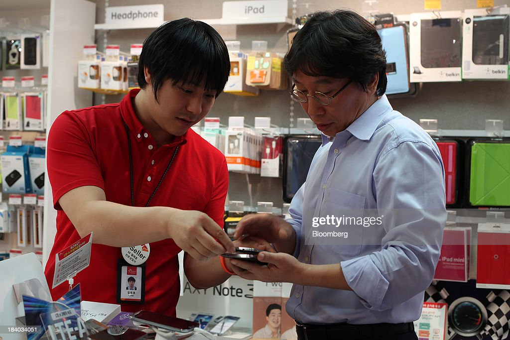An SK Telecom Co. employee, left, demonstrates a Samsung Electronics Co. Galaxy Round smartphone for a customer at one of the company's boutiques in the Jongro-gu area of Seoul, South Korea, on Friday, Oct. 11, 2013. Samsung will sell what it called the worlds first smartphone with a curved display as the largest handset maker moves toward devices with bendable screens in its competition with Apple Inc. Photographer: Woohae Cho/Bloomberg via Getty Images