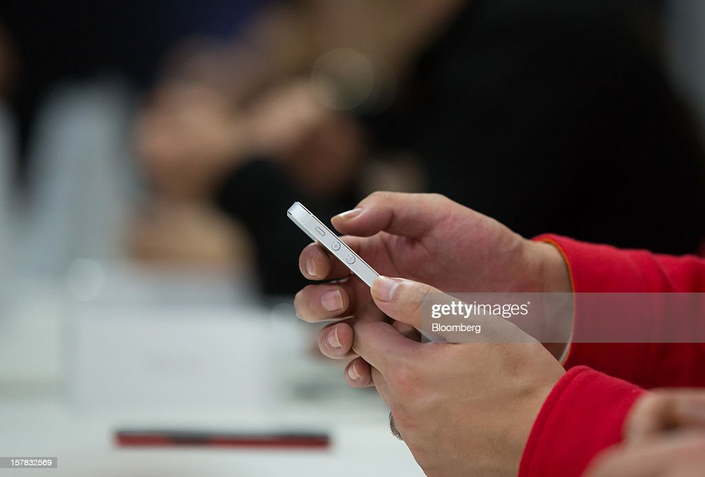 An SK Telecom Co. employee uses an Apple Inc. iPhone 5 during a launch event in Seoul, South Korea, on Friday, Dec. 7, 2012. The iPhone 5 went on sale in South Korea today. Photographer: SeongJoon Cho/Bloomberg via Getty Images