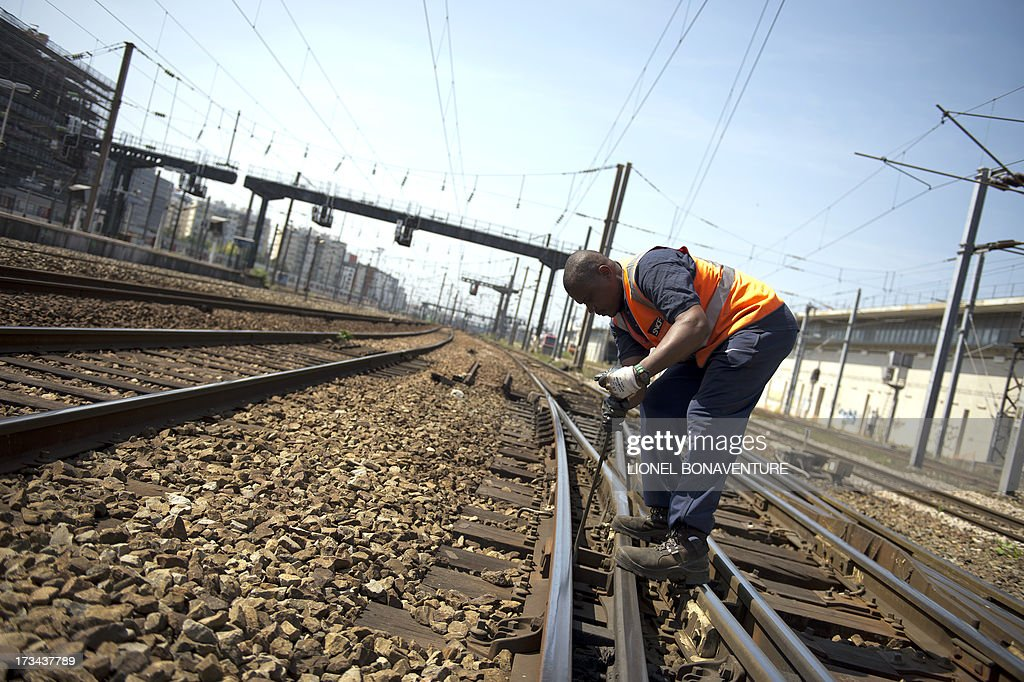 An SNCF agent checks a fishplate, a metal bar which joins the ends of two rails, on July 14, 2013 in Paris at Saint Lazare railway station. A defective fishplate could be the cause of the Bretigny-sur-Orge's train accident, according to the SNCF, France's national railway company. At least six people were killed and dozens injured on July 12, 2013 after a speeding train split in two and derailed at a station in the southern suburbs of Paris.