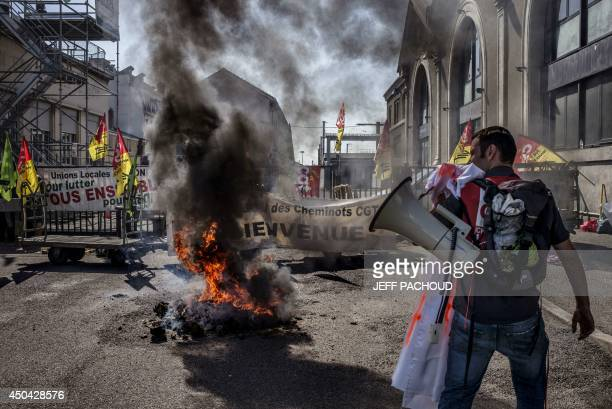 An SNCF employee is seen during a demonstration in front of the Perrache railway station on June 11 2014 in Lyon on the first day of a national...