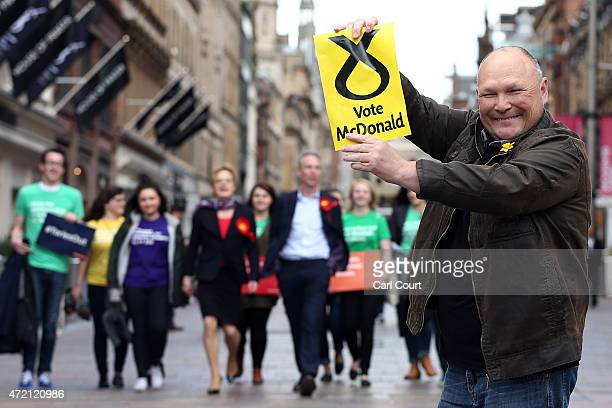 An SNP supporter holds a poster in front of Jim Murphy the leader of the Scottish Labour Party and comedian Eddie Izzard as they campaign on May 4...