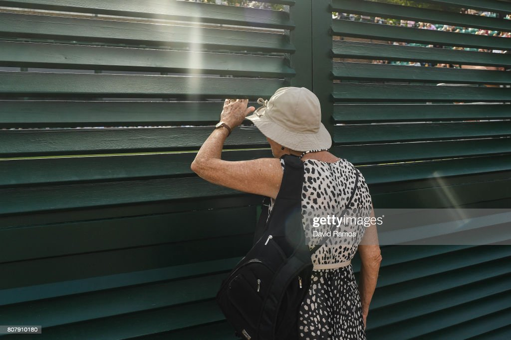 An spectator sneaks a look through the fence during the match between Timea Bacsinszky of Switzerland and Monica Puig of Puerto Rico on day two of the Wimbledon Lawn Tennis Championships at the All England Lawn Tennis and Croquet Clubon July 4, 2017 in London, England.