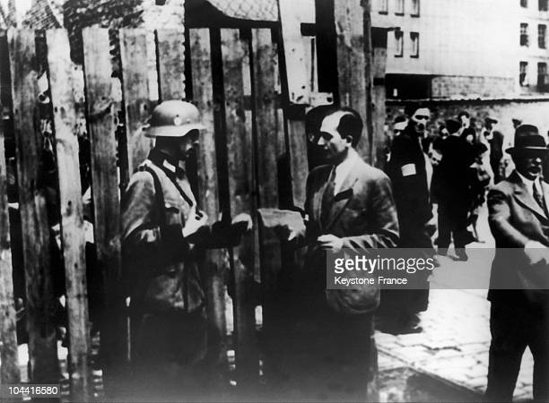 An SS soldier checking the papers of a Polish Jew exiting Warsaw's ghetto around 19401943