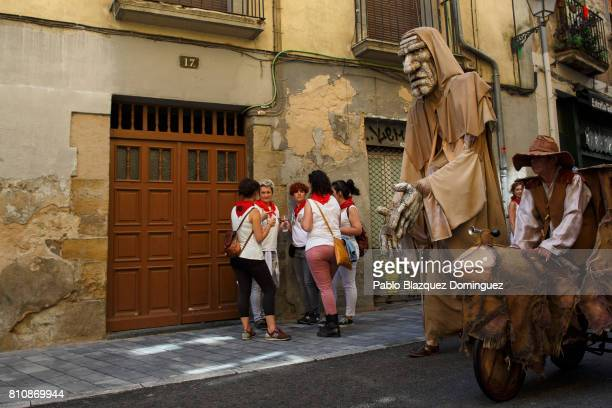 An street artist walks the street performing with a traditional giant made of recycled items during the third day of the San Fermin Running of the...