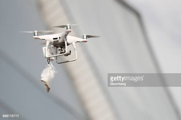 An SZ DJI Technology Co Phantom 4 drone carrying a bag of powder flies during a simulated chemical terrorism crisis as part of an antiterror drill on...
