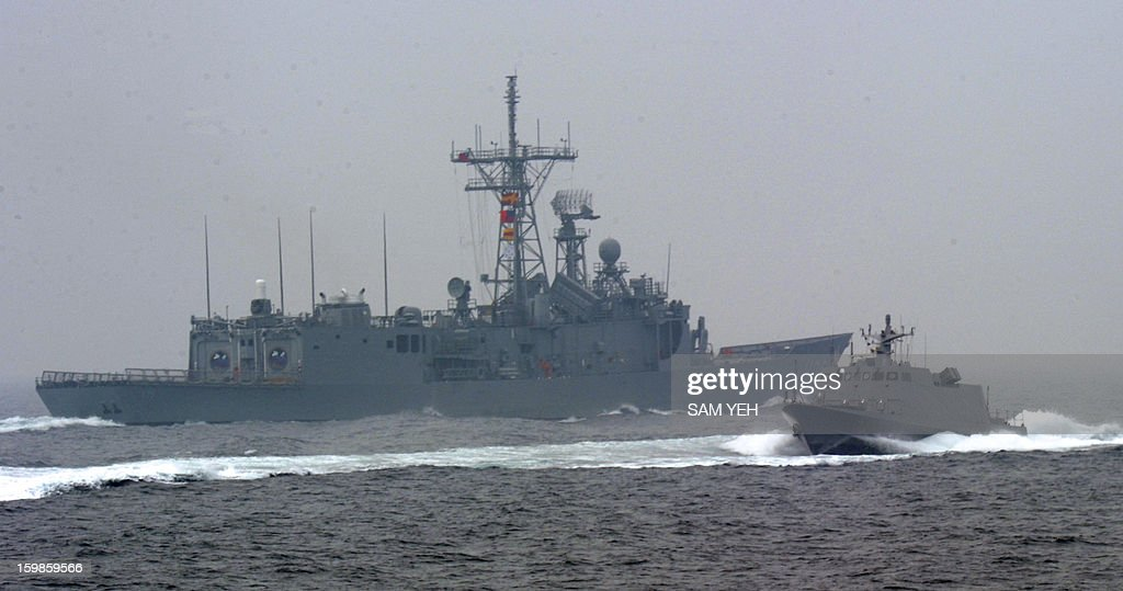 An Taiwan made Kuang Hua Six missile boat (R) passes a Perry-class frigate on the sea near the Tsoying naval base in southern Kaohsiung city on January 22, 2013. Taiwan's frigates, missile boats, rescue helicopter and submarines are taking part in an annual training before the coming lunar new year. AFP PHOTO / Sam Yeh