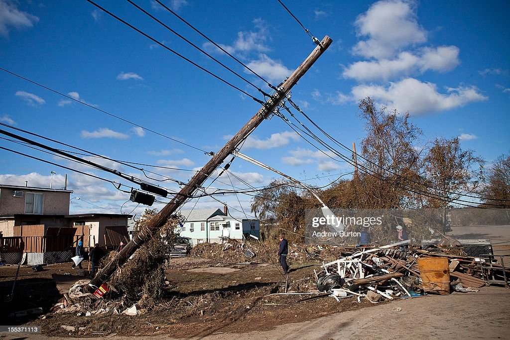 An telephone pole leans over the road in the Midland Beach neighborhood of Staten Island on November 3, 2012 in New York City. As clean up efforts from Superstorm Sandy continue, colder weather and another storm predicted for next week are beginning to make some worried.