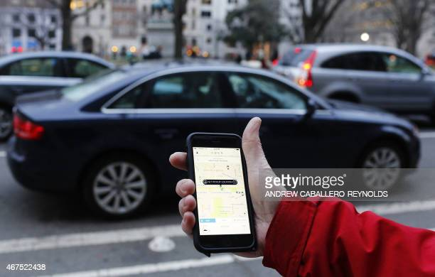 An UBER application is shown as cars drive by in Washington DC on March 25 2015 Uber said it was ramping up safety in response to rape allegations...