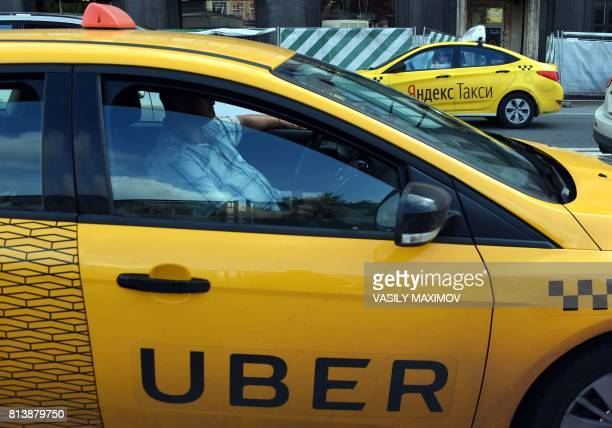 An Uber car and a YandexTaxi car drive on a street in Moscow on July 13 2017 Uber on July 13 2017 announced that it was merging in Russia and five...