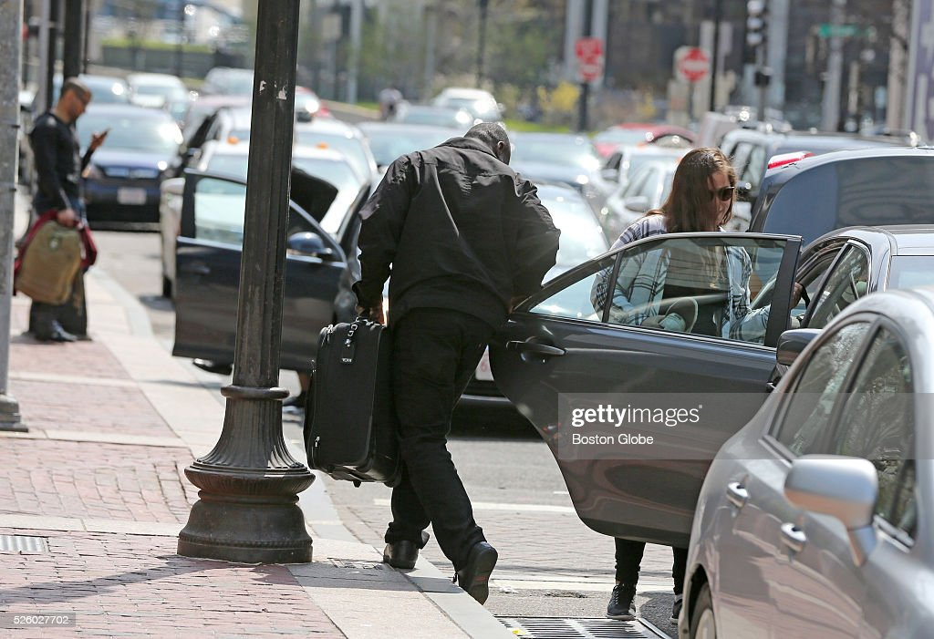 An Uber driver helps out a passenger with luggage outside South Station in Boston on April 22 2016