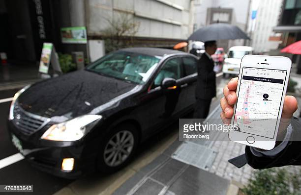 An Uber Japan Co employee holds an Apple Inc iPhone 5s showing a map on the Uber application for a photograph during a demonstration in Tokyo Japan...