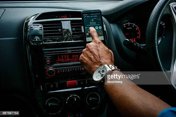 An Uber Technologies Inc car service driver uses a navigation app on his smartphone while driving in Kuala Lumpur Malaysia on Friday Aug 5 2016...