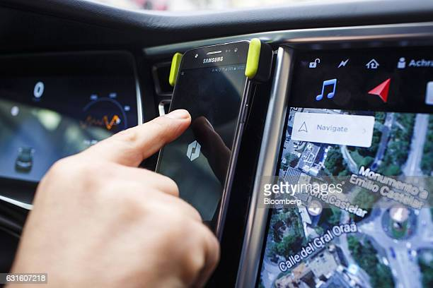 An Uber Technologies Inc driver uses the company's smartphone app inside a Tesla Motors Inc Model S electric automobile in Madrid Spain on Friday Jan...