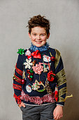A child wearing a homemade ugly Christmas sweater using ornaments, ribbons and garland on a gray backdrop.