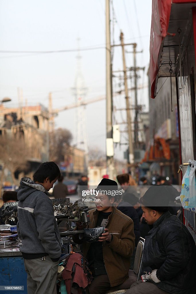 An Uighur man in the street mends shoes in Kashgar, on December 10, 2012 in Kashi, China. Kashgar is home to the ethnic Uyghur Muslim community.