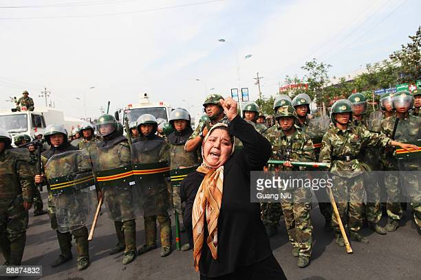 An Uighur woman protests in front of policemen at a street on July 7 2009 in Urumqi the capital of Xinjiang Uighur autonomous region China Hundreds...