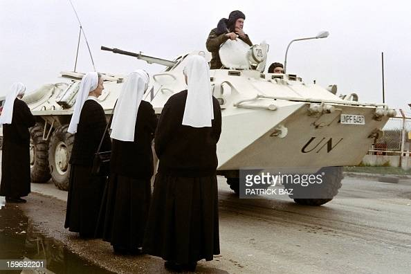 An Ukrainian armoured vehicle passes Catholic nuns waiting to be evacuated on a UN convoy out of Sarajevo on November 05 1992 AFP PHOTO PATRICK BAZ