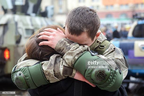 An Ukrainian policeman embraces his wife during a ceremony in Kharkiv northeastern Ukrainian on January 30 before his departure to the east of the...